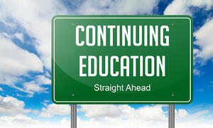 Highway Signpost with Continuing Education wording on Sky Background